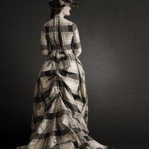 A portrait of a woman wearing a long plaid dress and a feather hat.