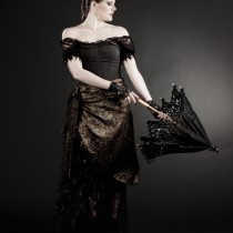 A woman wearing a Gothic period dress opening an umbrella.