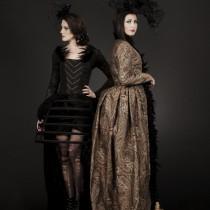 Two women wearing Gothic period dress.
