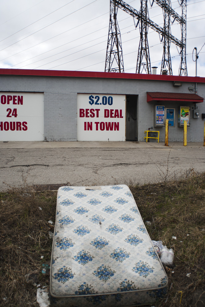 A mattress on the grass outside of an industrial builing with advertising in the background.
