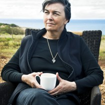 A woman wearing a necklace sitting on a chair having a tea or coffee.