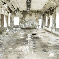 A large room with peeling paint and graffiti