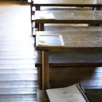Wooden desks lined up in a row in a classroom