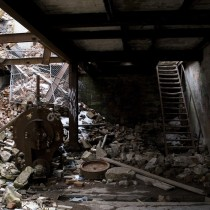 A building basement strewn with bricks and metal debris.